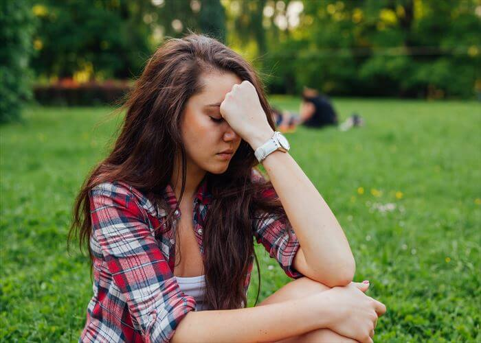 Girl sitting in  the park on the grass. She has headache. What a terrible day