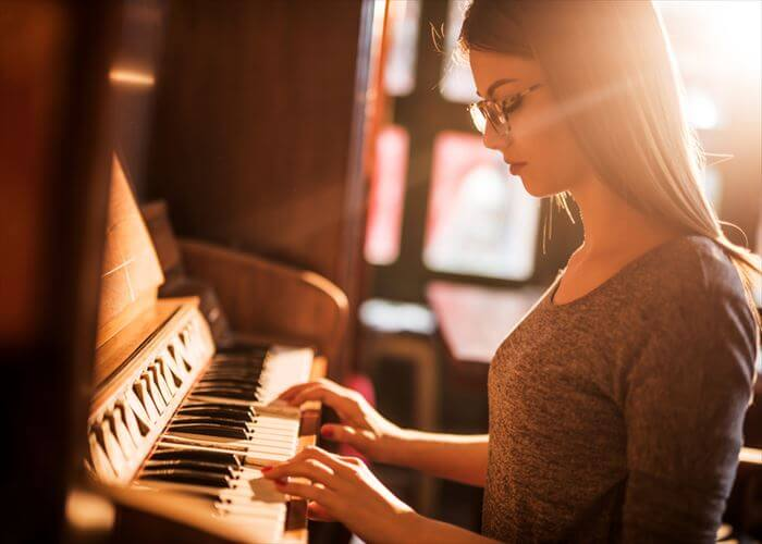 Young female pianist enjoying while practicing on retro styled piano.