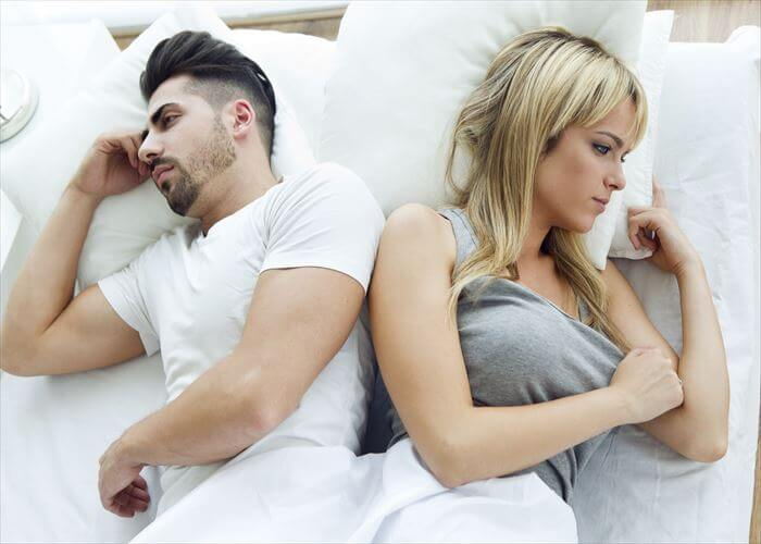 Portrait of upset couple lying back to back in bed