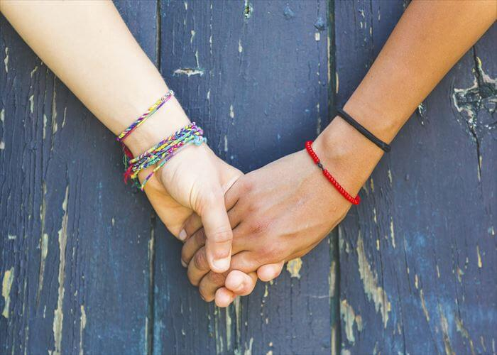 Two women holding hands with a wooden background. One is caucasian, the other is black. Multicultural, homosexual love and friendship concepts.