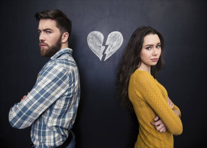 Unhappy young couple standing with arms crossed over background of chalkboard with drawn broken heart