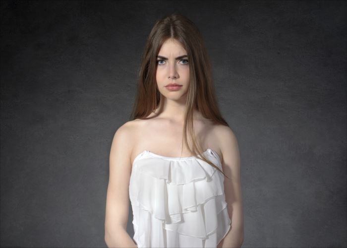 Concept human emotions. Woman shows a grudge against a dark background