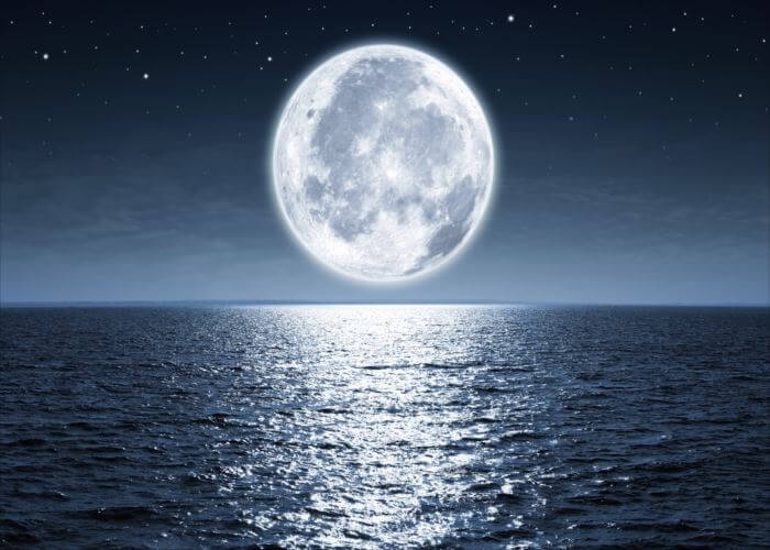 Full moon rising over empty ocean at night with copy space