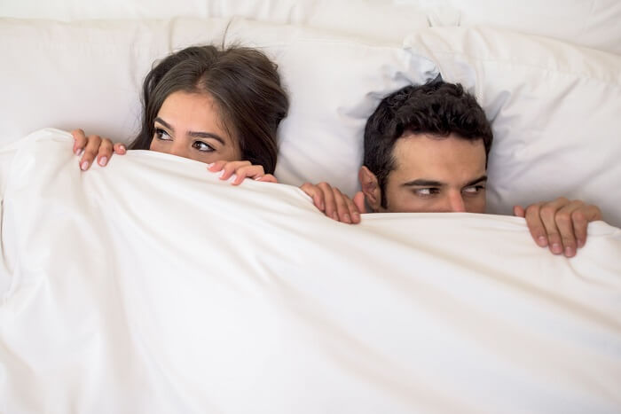 Portrait of a scared couple in bed with man and woman looking very anxious