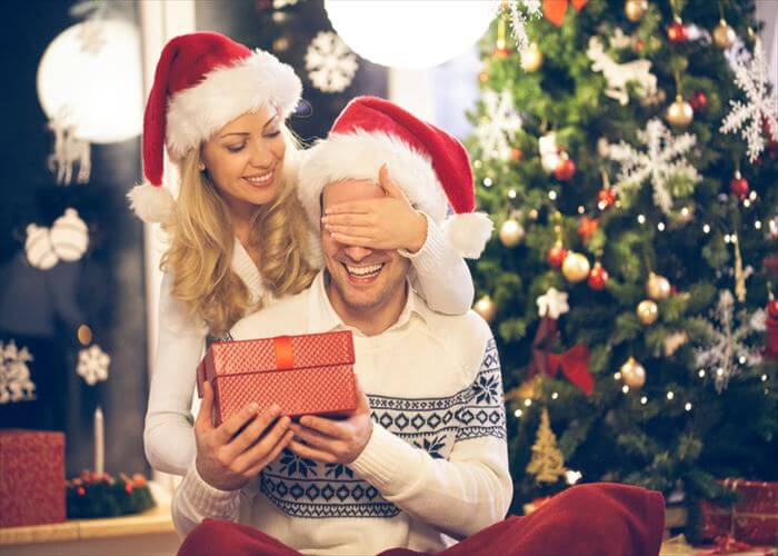 Young man and woman in Santa hat with Christmas present.