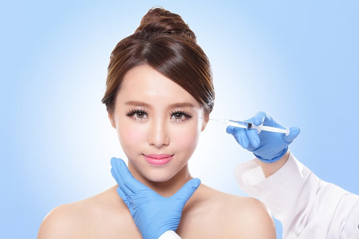 Close up of cosmetic injection to the pretty woman face. Isolated on blue background, asian