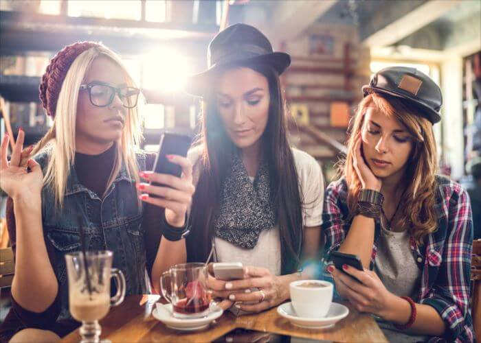 Female friends sitting in a cafe while each of them is using their own cell phone.