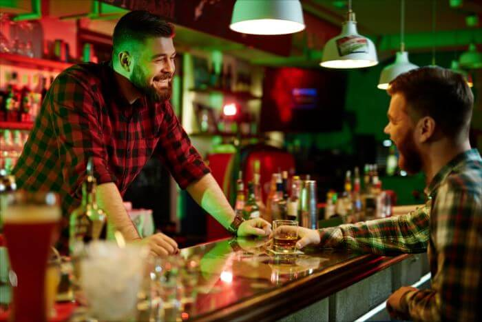 Happy barman talking to client in bar