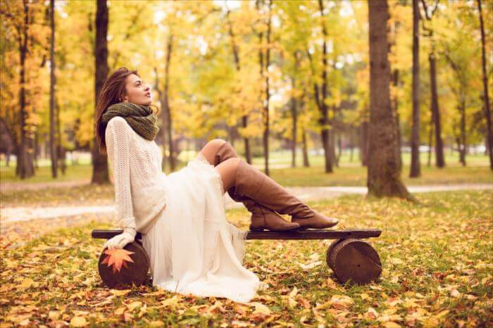 Beautiful girl sitting on a bench in park and enjoy while watching autumn colors all around. He's wearing a white skirt, black leather boots, handmade sweater and green scarf. She is relaxed, happy and looks into the distance.