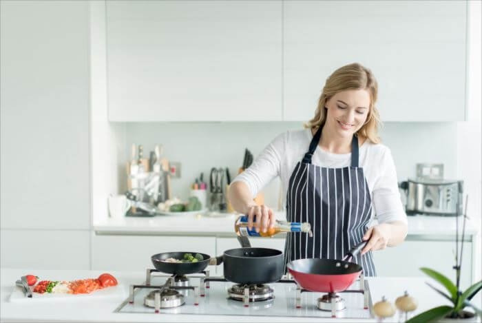Happy woman cooking at home wearing an apron - healthy eating concepts