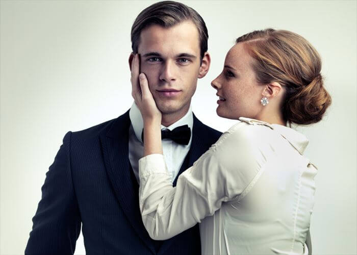 A cropped studio portrait of a dapper young man with a beautiful girl on his arm