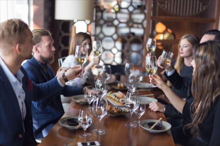 Group of friends toasting with white wine in restaurant