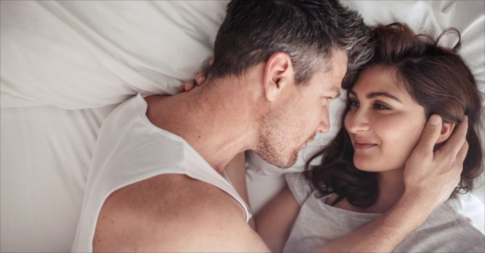 Overhead close up of young couple lying in bed together. Romantic couple in love looking at each other.