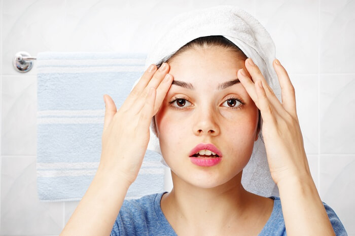 Young girl looking in her bathroom with a towel on her head.