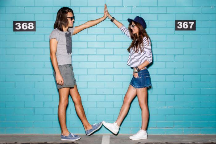 Young modern happy couple in love making frame with their hands and legs in front of a blue brick wall. They are wearing sunglasses and smile to each other.