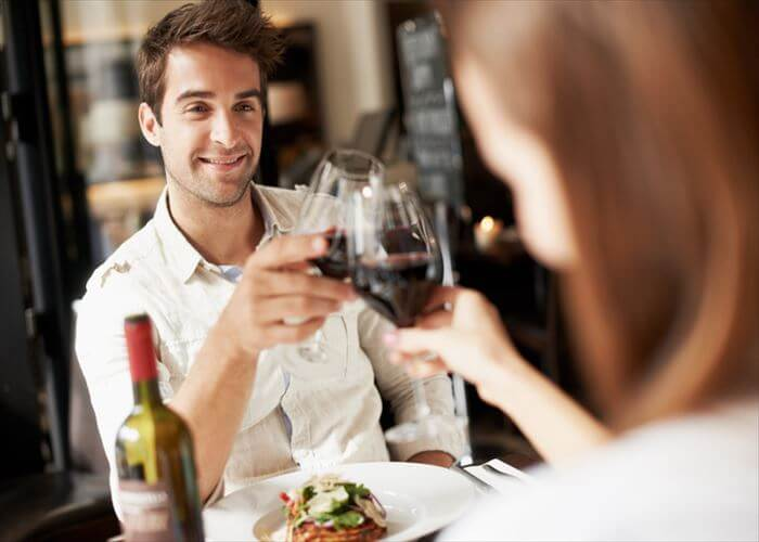 Smiling young man clinking glasses with his girlfriend while at dinner