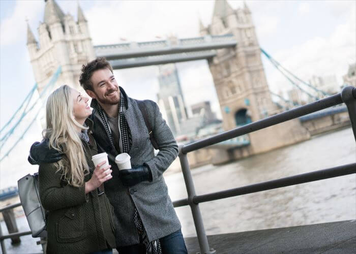 Happy couple on a date walking around London drinking a cup of coffee to go