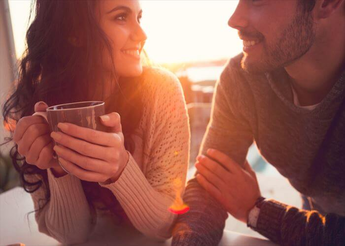 Couple drinking coffee and talking. They are looking at each other at sunrise or sunset. He has a beard.